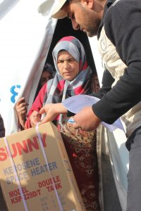 SRD staff delivering heater to refugee woman
